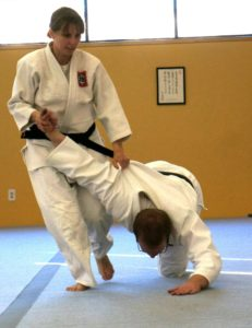 Woman in Aikido dogi taking a man in an Aikido dogi to the mat