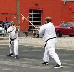two black-belt Aikido instructors prctice outside with wooden Jo